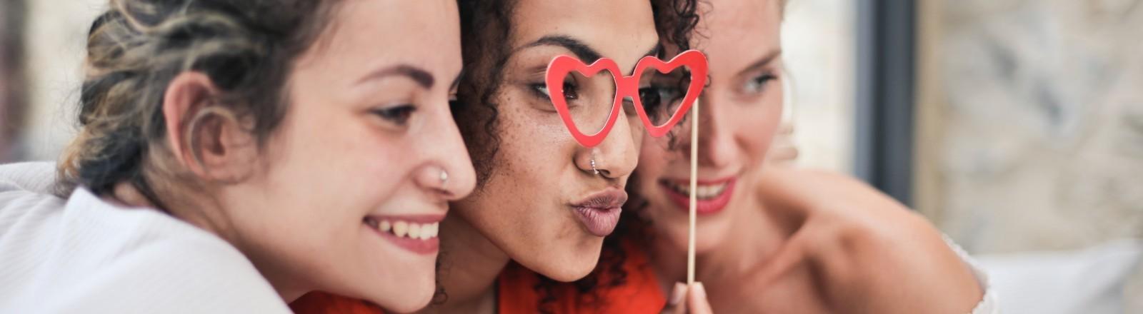 Drei Freundinnen schauen in die Kamera