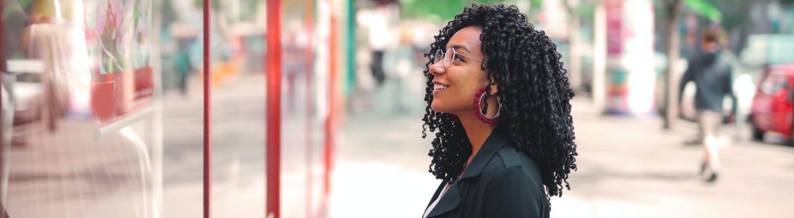 Eine Frau schaut grinsend in ein Schaufenster