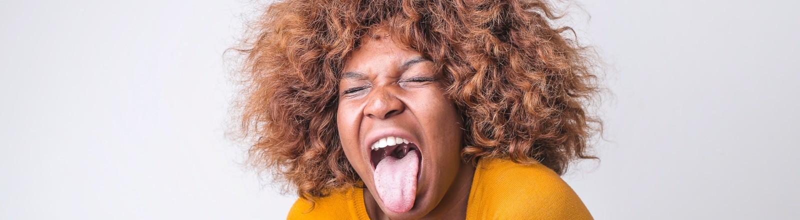 Eine Frau streckt angeekelt ihre Zunge raus