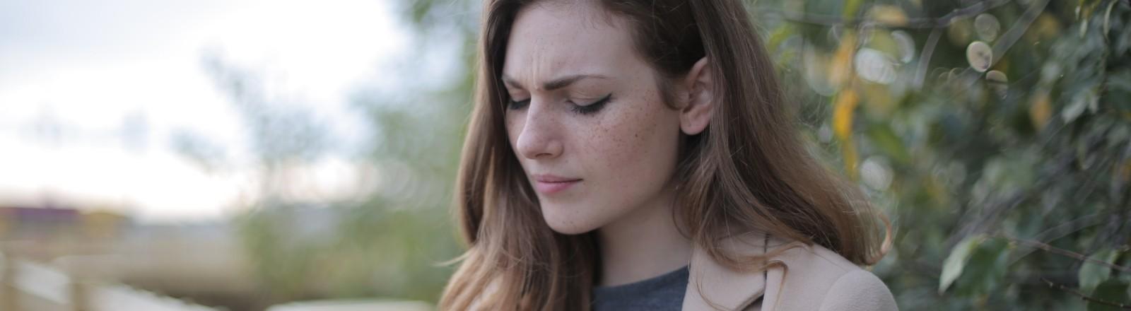 Eine junge Frau schaut gekränkt auf ihr Smartphone