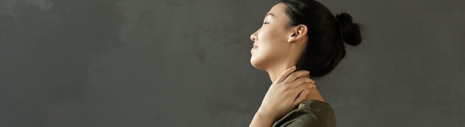Eine Frau sitzt auf dem Bett und reibt sich den Nacken