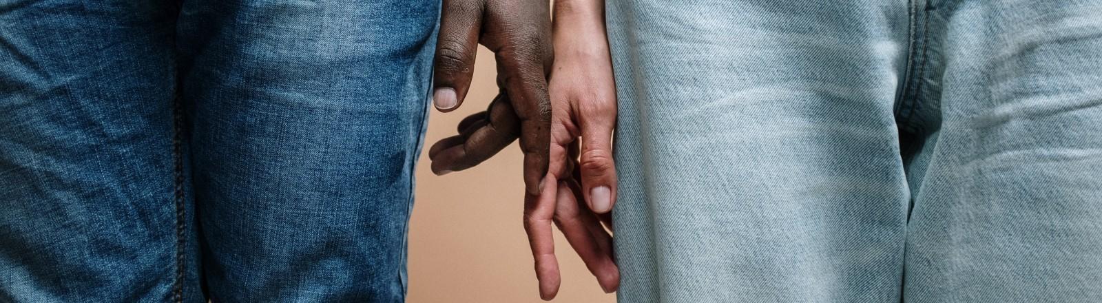 Eine schwarze und eine weiße Hand berühren sich ganz leicht