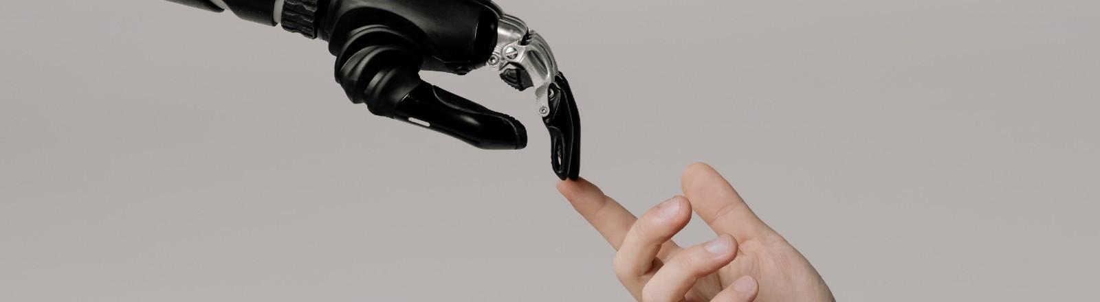 Eine Roboterhand berührt einen menschlichen Finger