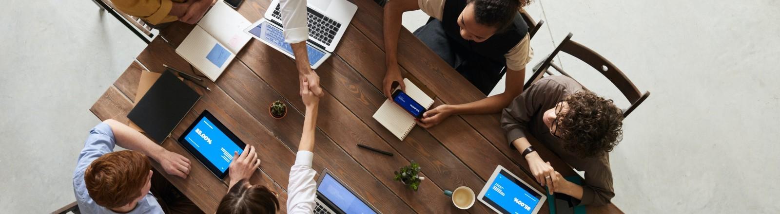 Zwei Menschen geben sich über eine Tisch die Hand in einem Meeting