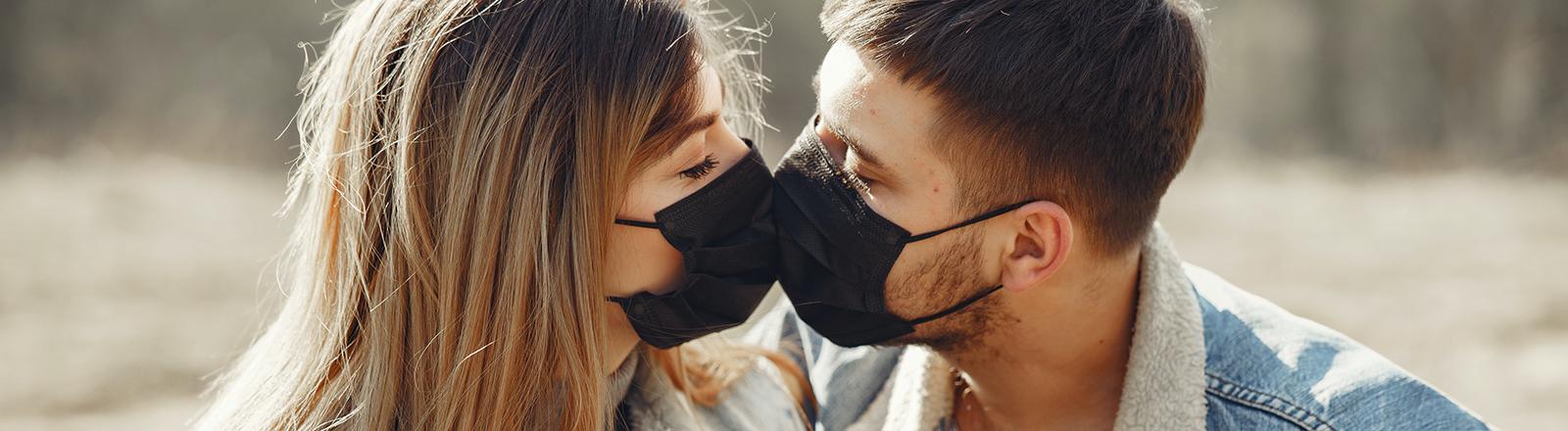 Paar küsst sich mit Maske.
