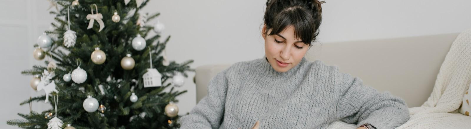 Eine Frau sitzt vor einem Weihnachtsbaum und streichelt ihren Hund