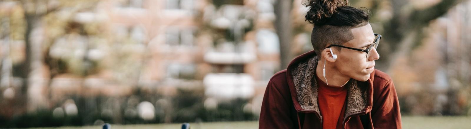 Ein junger Mann sitzt auf der Parkbank und schaut nach rechts