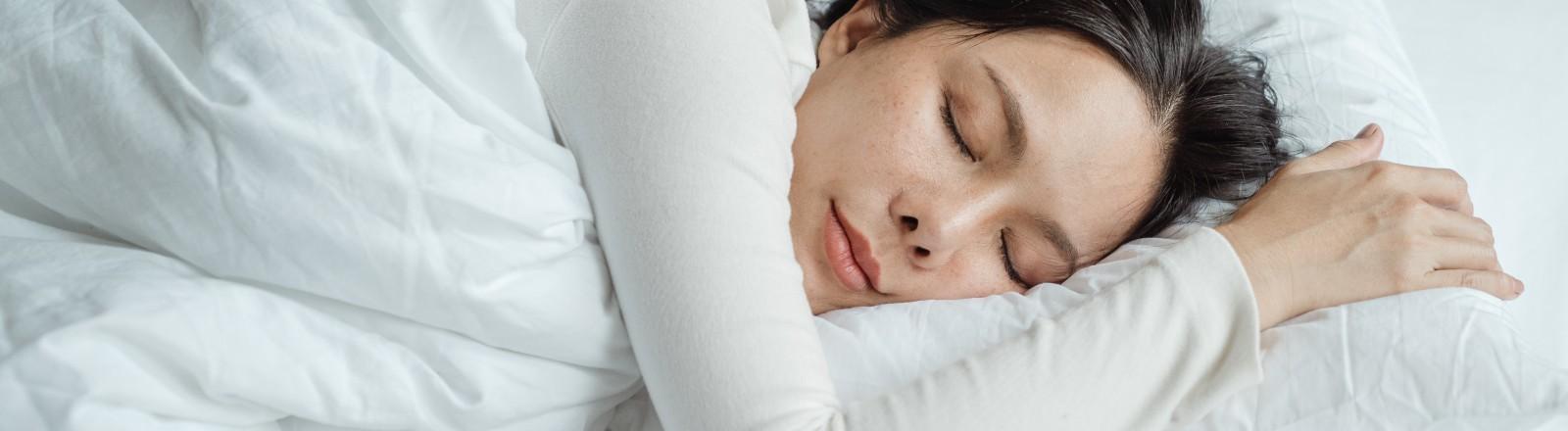 Die Frau liegt im Bett und schläft