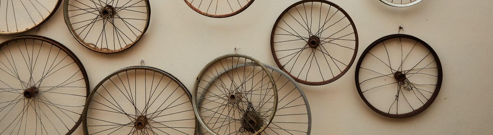 Alte Räder von Fahrrädern hängen an einer Wand