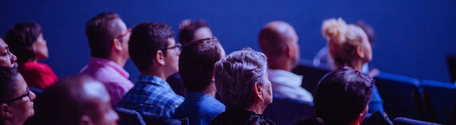 Ein Publikum sitzt in einem blauen Raum