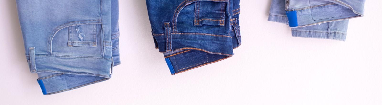 Drei Jeanshosen in unterschiedlichen Blautönen