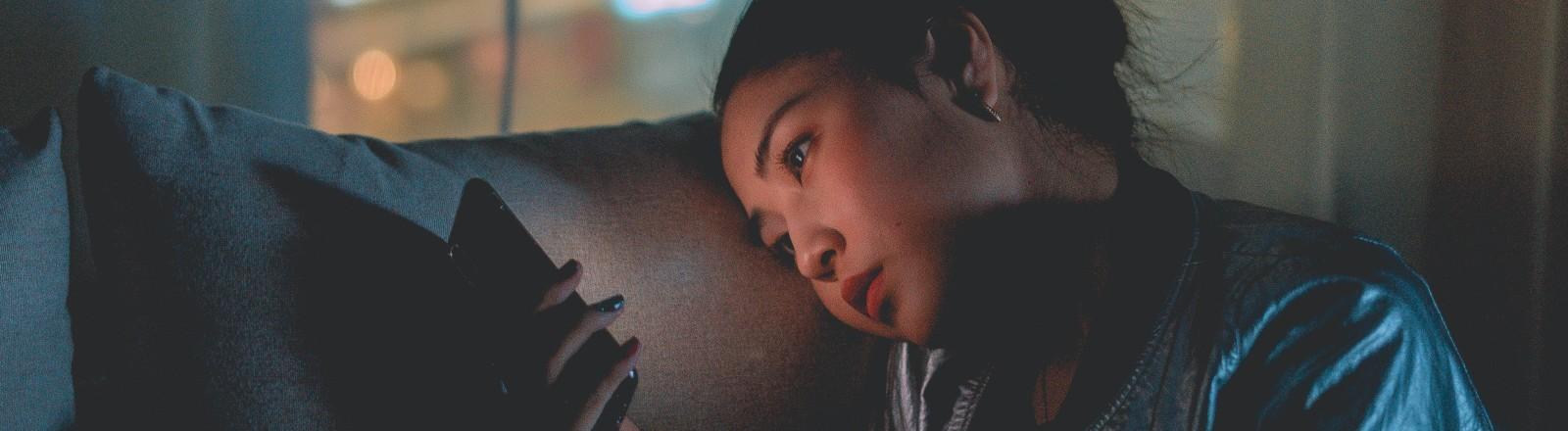 Eine Frau sitzt auf der Couch und starrt in ihr Handy