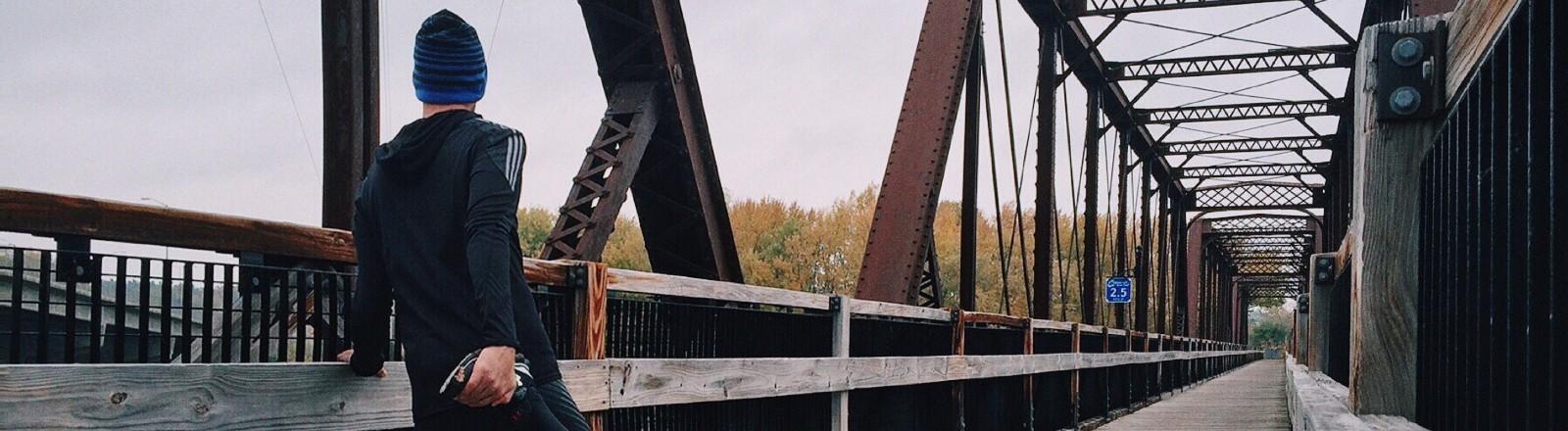 Ein Mann dehnt sich auf eine Brücke