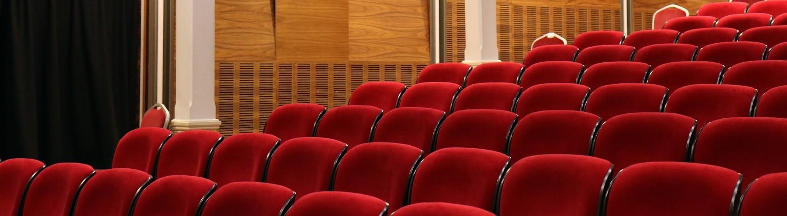 Ein leeres Theater mit roten Samtsitzen