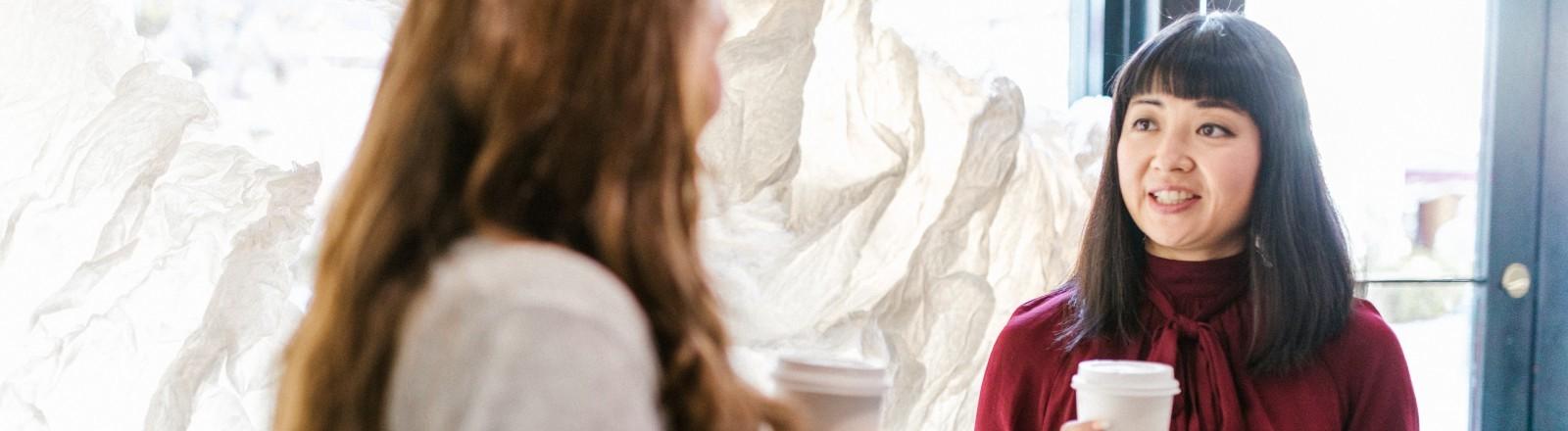 Zwei Frauen unterhalten sich mit Kaffeebechern im Flur