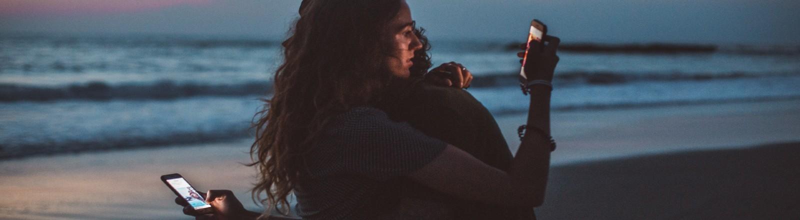 Paar am Strand mit Smartphones
