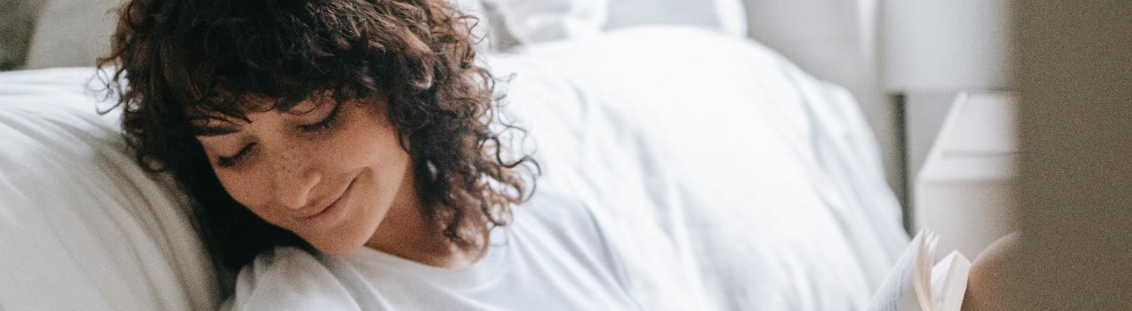 Eine Frau lehnt an ein Bett und lächelt