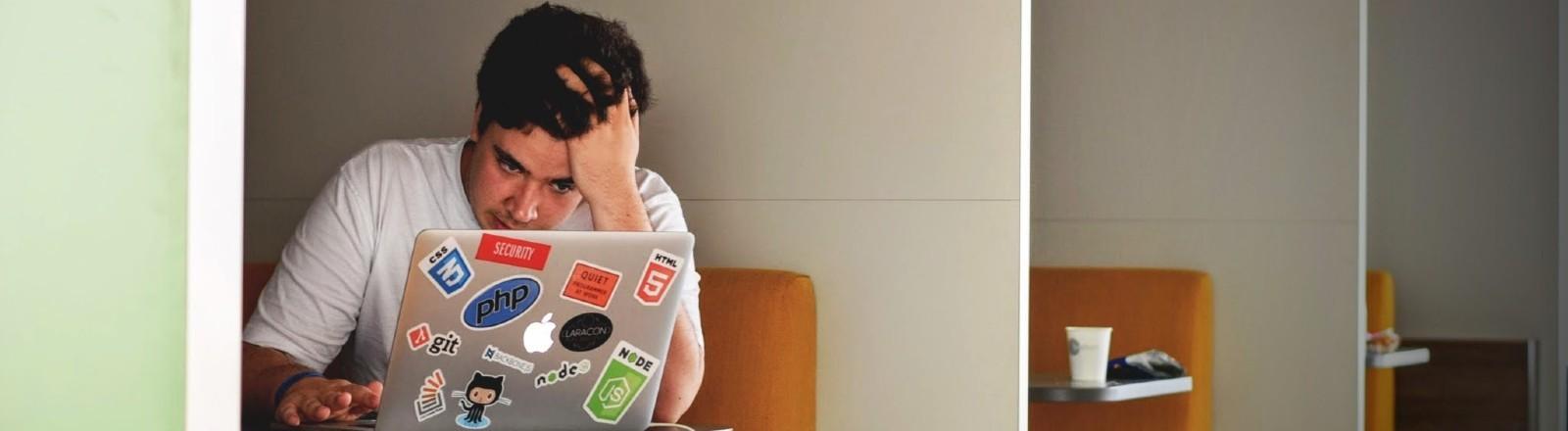 Ein Mann sitzt geknickt vor seinem Laptop