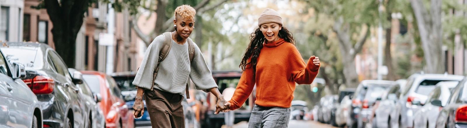 Ein lesbisches Paar fährt zusammen Longboard