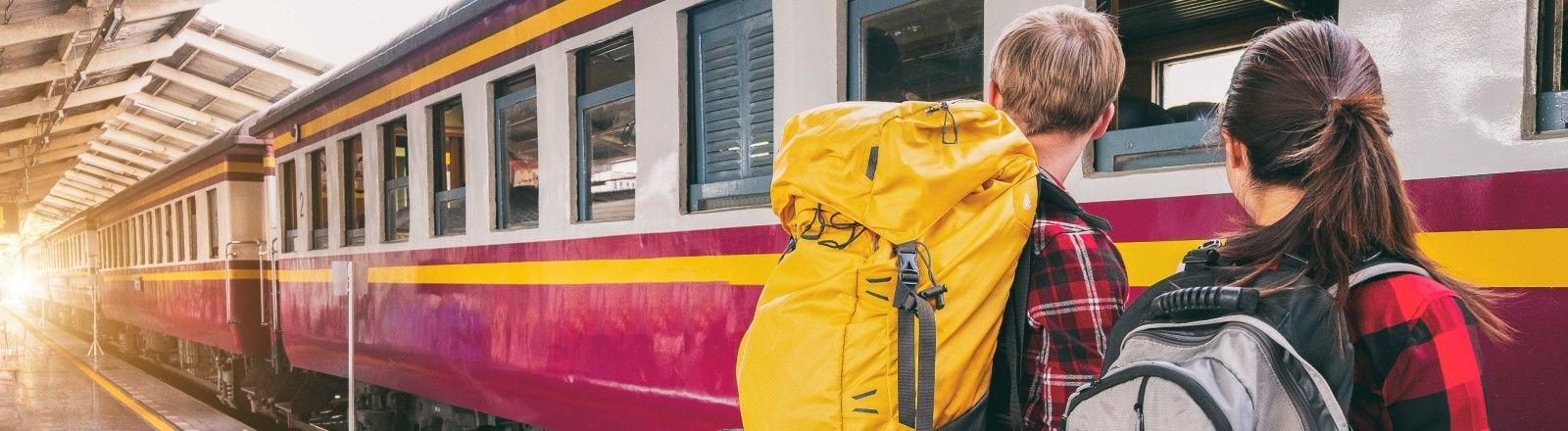 Zwei Backpacker warten auf den einfahrenden Zug