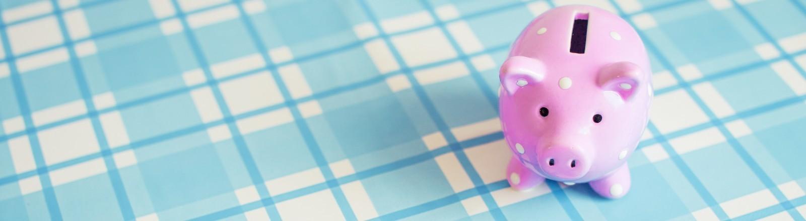 Ein rosé Sparschwein auf einer hellblauen Tischdecke