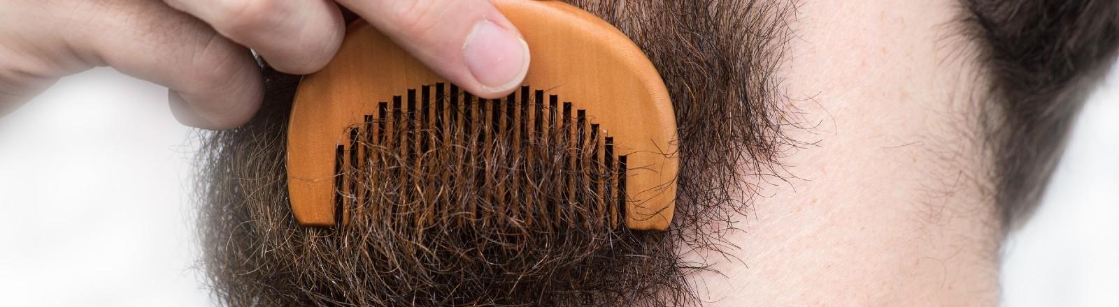 Ein Mann kämmt durch seinen Bart