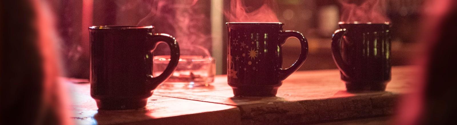 Drei Tassen mit Glühwein, die dampfen