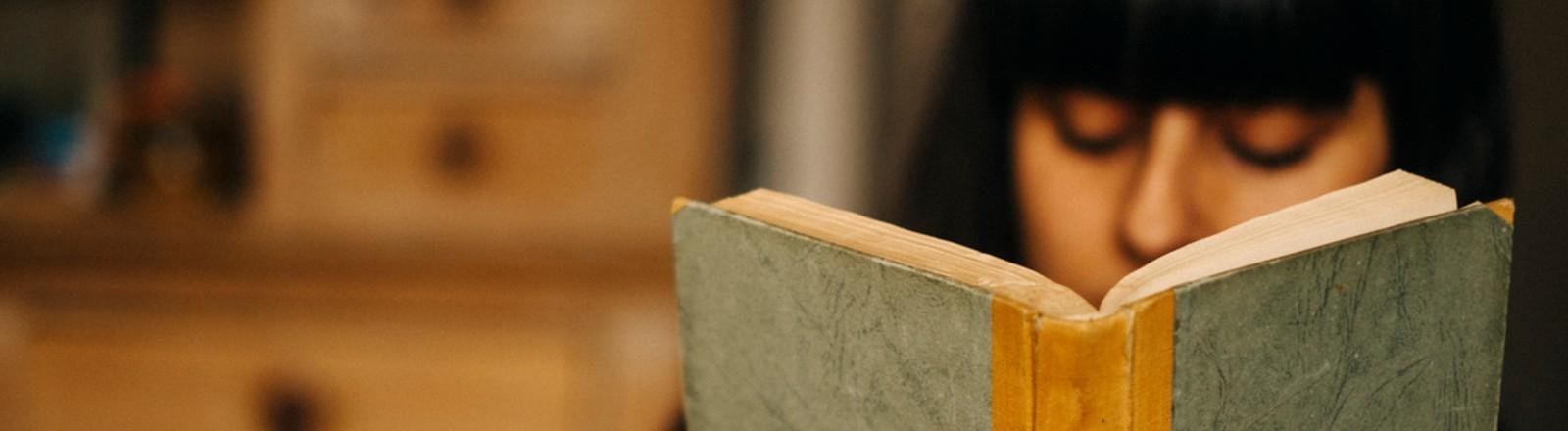 Eine Frau mit rot lackierten Fingernägeln liest ein Tagebuch