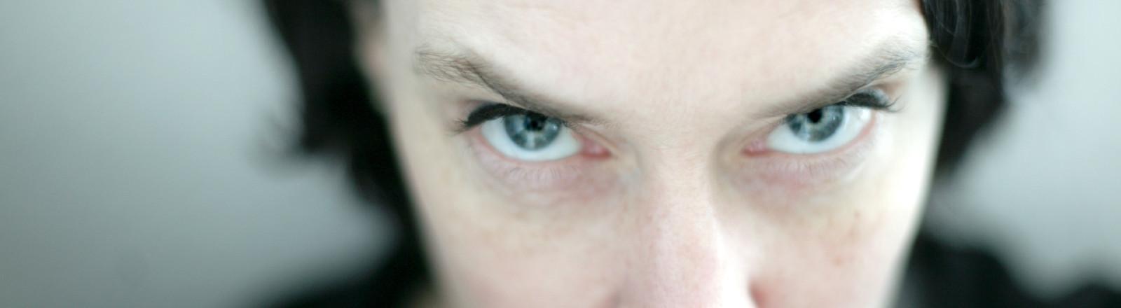 Eine Frau blickt mit Rachegelüsten oder hasserfüllt.