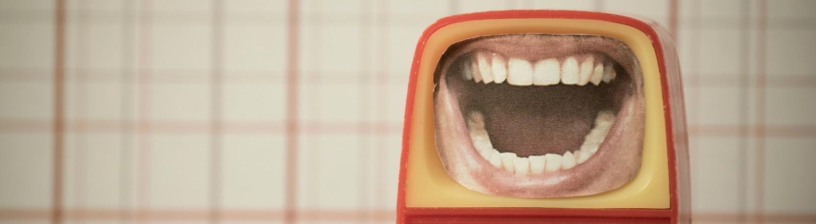 Ein Mund, der aus einem Miniatur-TV rausschaut