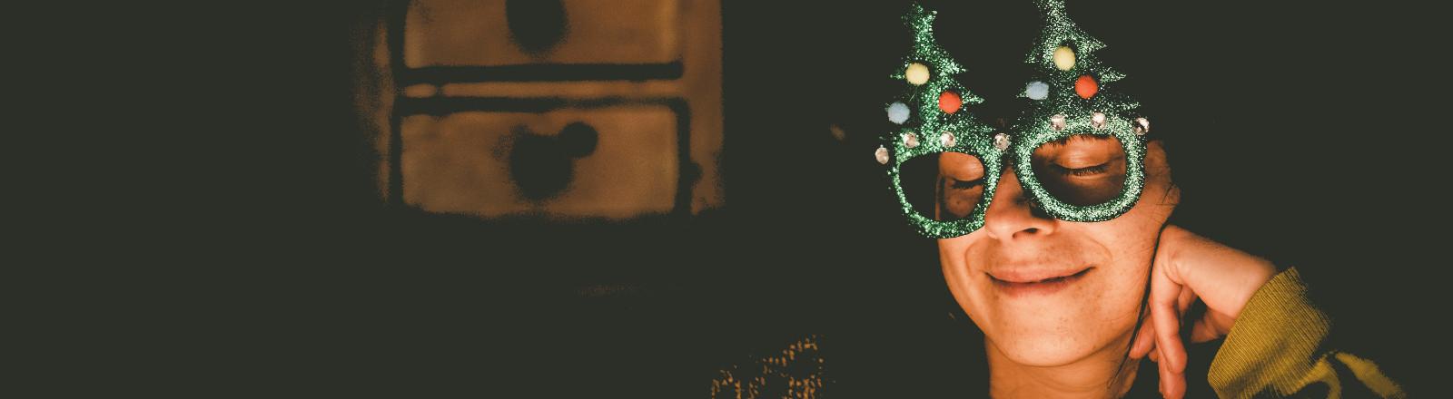 Frau feiert entspannt Weihnachten mit einer lustigen Weihnachtsbrille.