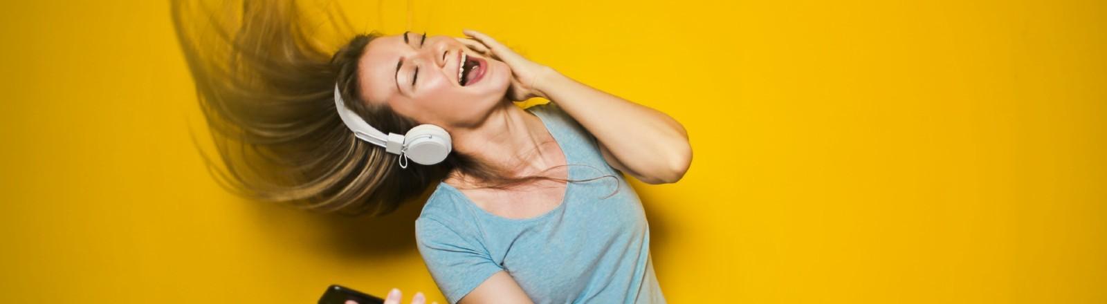 Frau mit Kopfhörern und Smartphone, die zu Musik tanzt, ihre Haare fliegen durch die Luft.