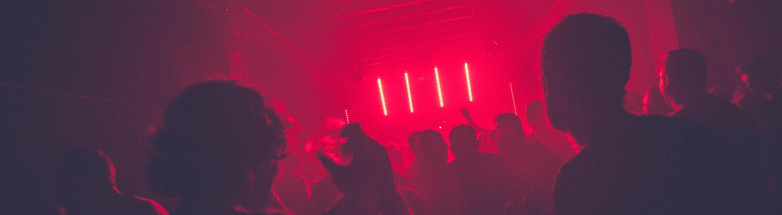 Menschen feiern im roten Neon-Licht.