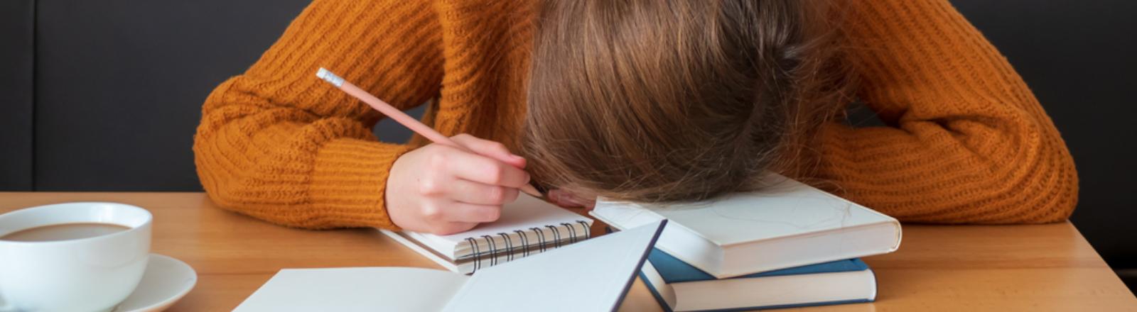 Gestresste Frau legt ihren Kopf auf den Schreibtisch