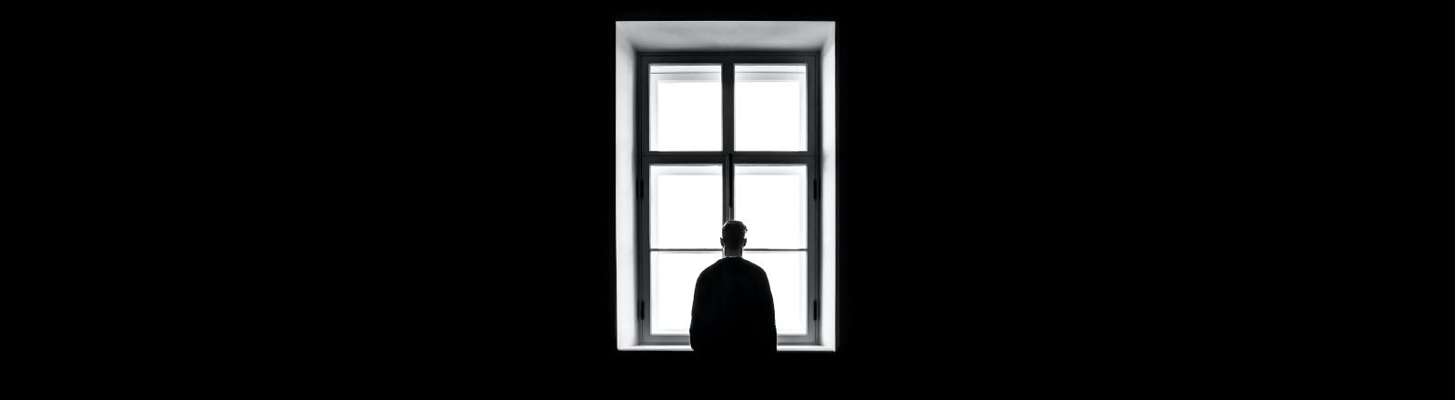 mann steht vor einem Fenster