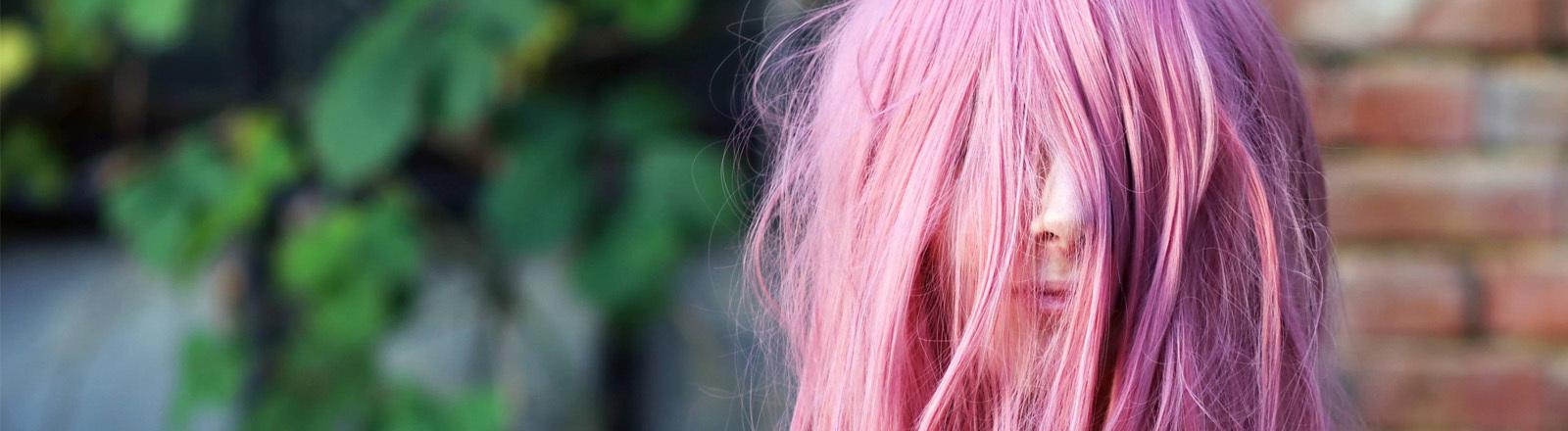 Mädchen mit pinken Haaren vorm Gesicht