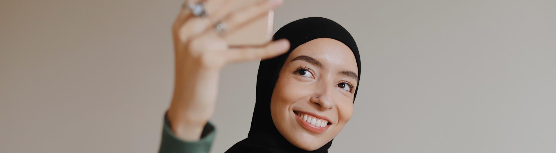 Eine junge Frau mit Kopftuch lächelt in ihr Smartphone