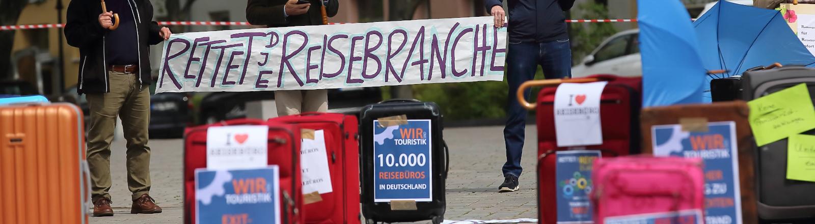 Menschen demonstrieren für die Rettung der Reisebranche