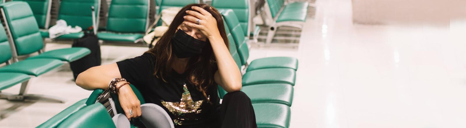 Eine Frau sitzt erschöpft in einer Flughafen-Wartehalle