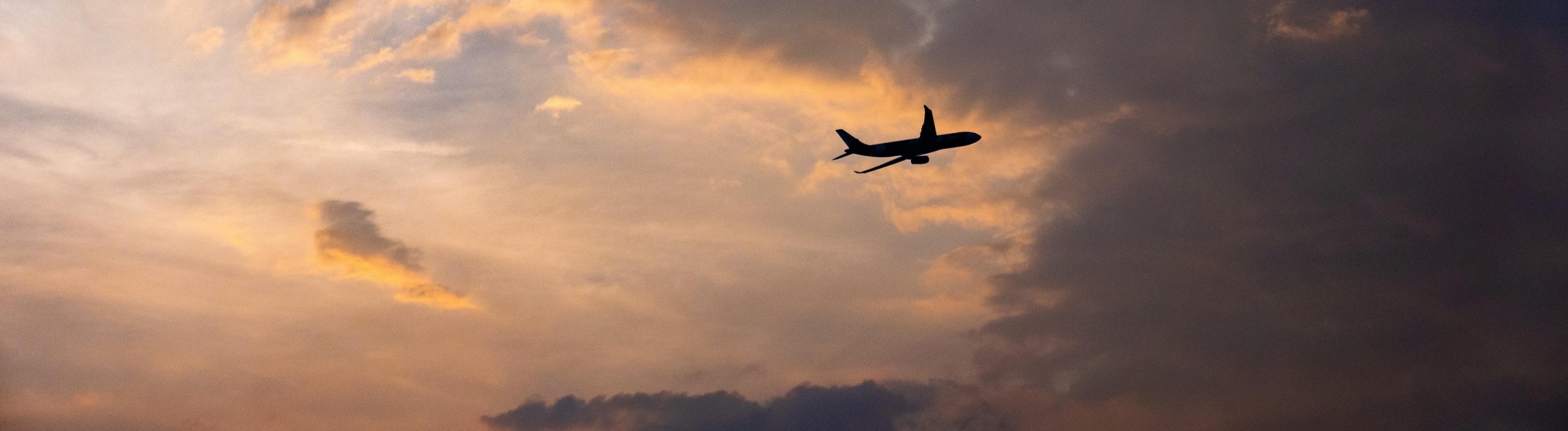 Flugzeug am Abendhimmel, fliegt in eine dunkle Wolke
