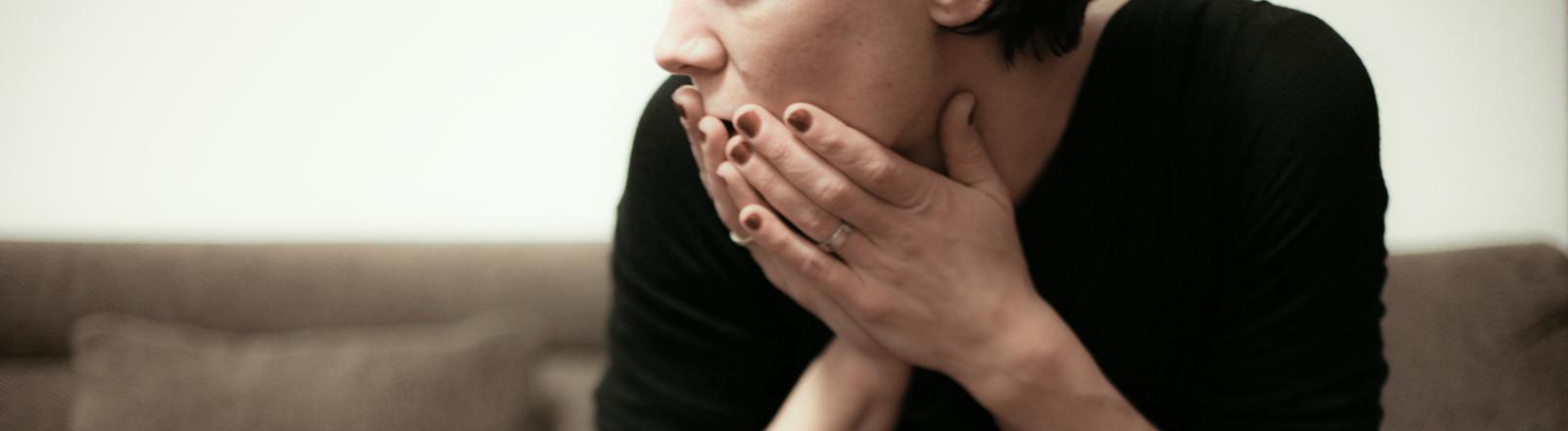 Eine Frau sitzt auf dem Sofa und schlägt erschrocken ihre Hände vor den Mund.