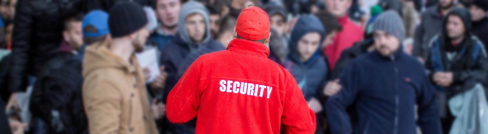 Sicherheitsmitarbeiter von hinten vor Menschenmenge