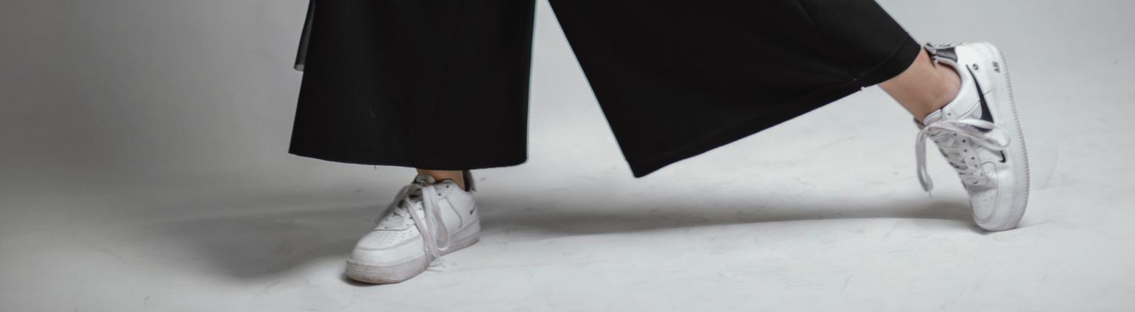 Person mit schwarzem Jumpsuit und weißen Sneakern.