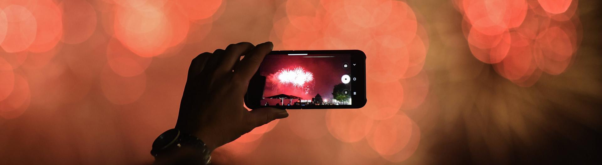 Feuerwerk auf einem Smartphonebildschirm, im Hintergrund verschwommene Lichter