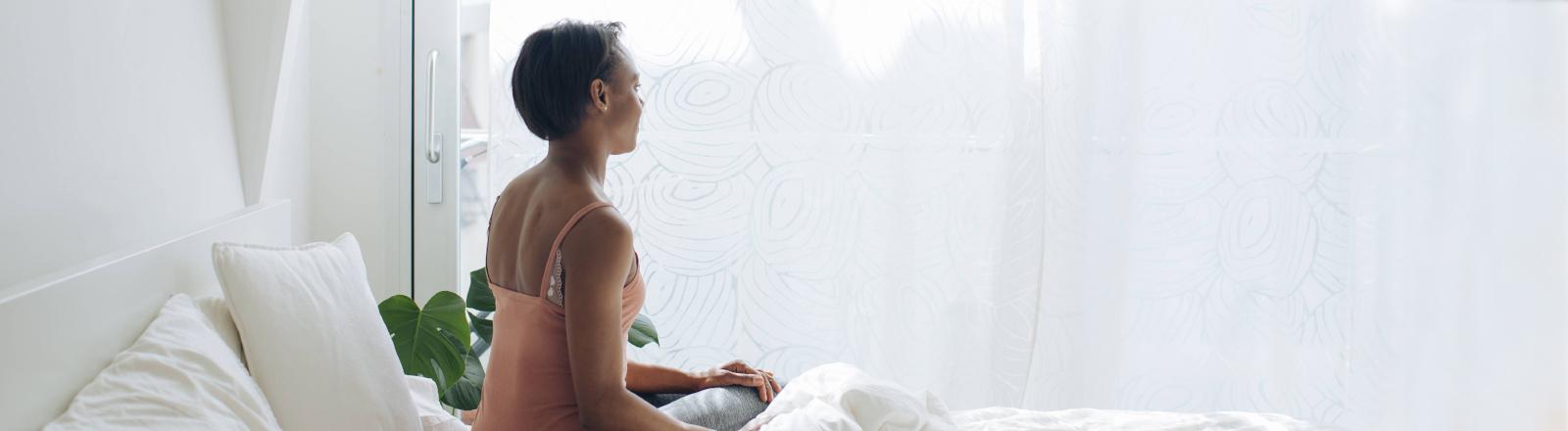 Frau sitzt alleine auf Bett