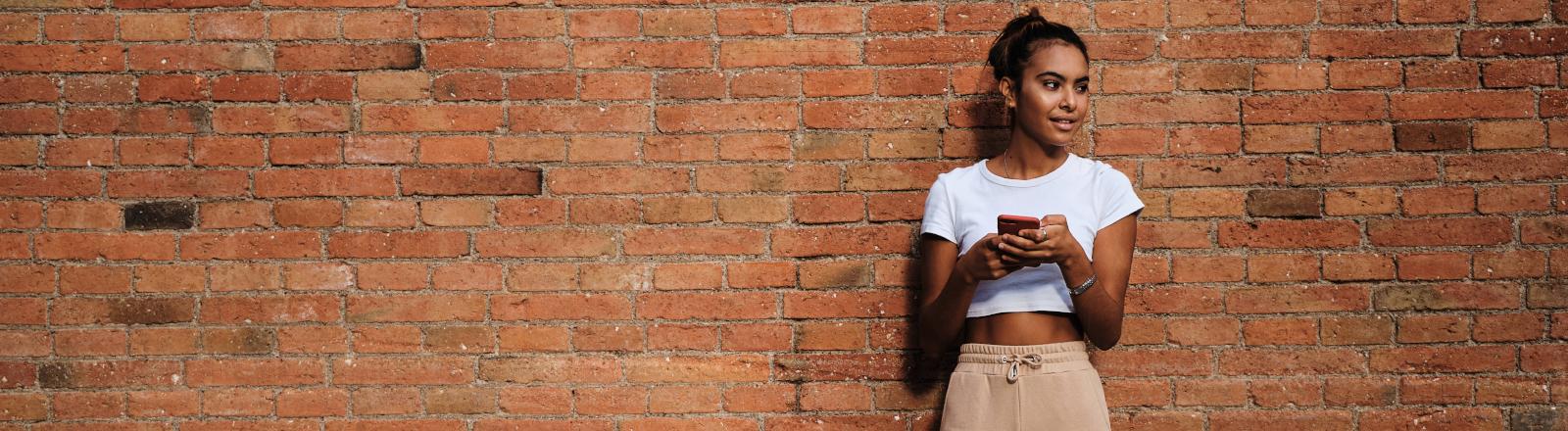 Junge Frau steht mit ihrem Smartphone an einer Wand
