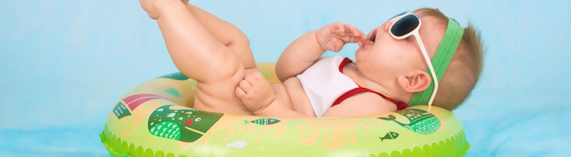 Baby liegt mit Sonnenbrille auf einem Schwimmreifen