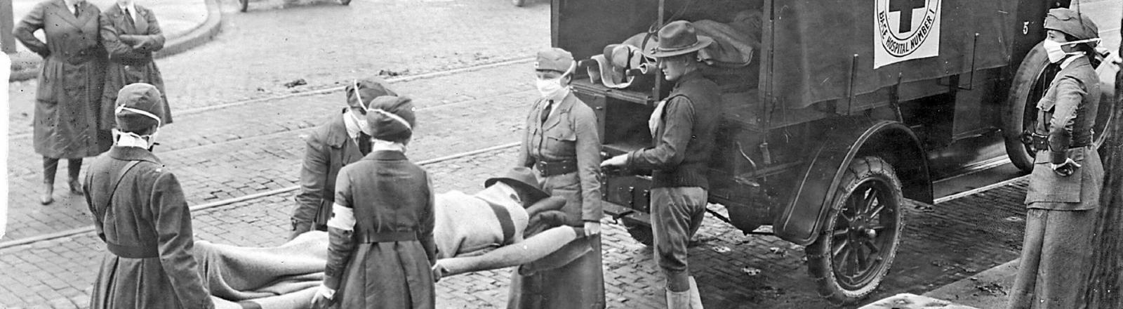 Das amerikanische rote Kreuz transportiert ein Opfer der spanischen Grippe aus seinem Haus, 1918. St. Louis