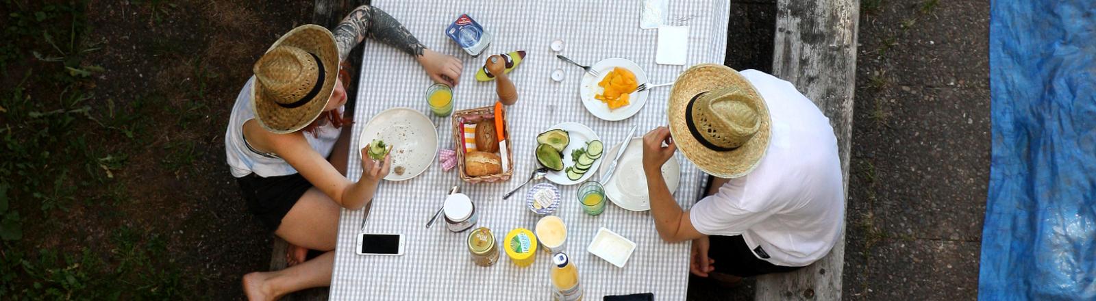 Eine Mann und eine Frau essen an einem großen Tisch Frühstück
