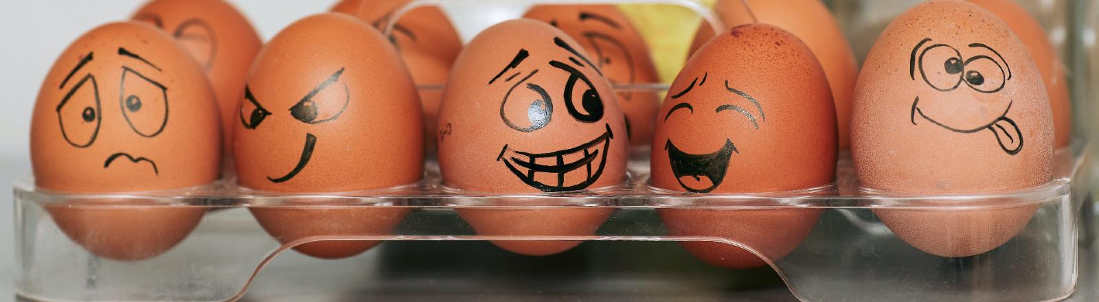 Eier mit aufgemalten Gesichtern